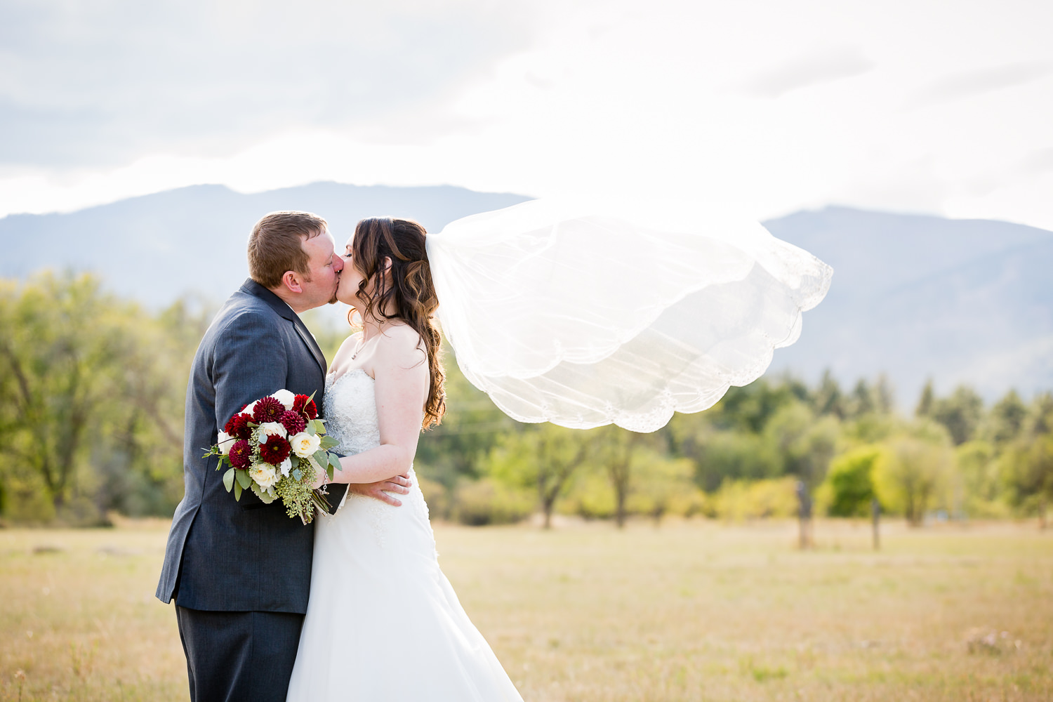 heritage-hall-missoula-montana-bride-groom-kissing-while-veil-flies.jpg