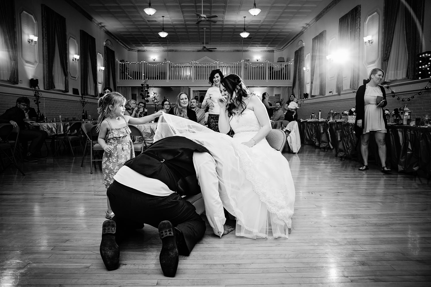 heritage-hall-missoula-montana-bride-laughs-while-flowergirl-helps-remove-garter.jpg