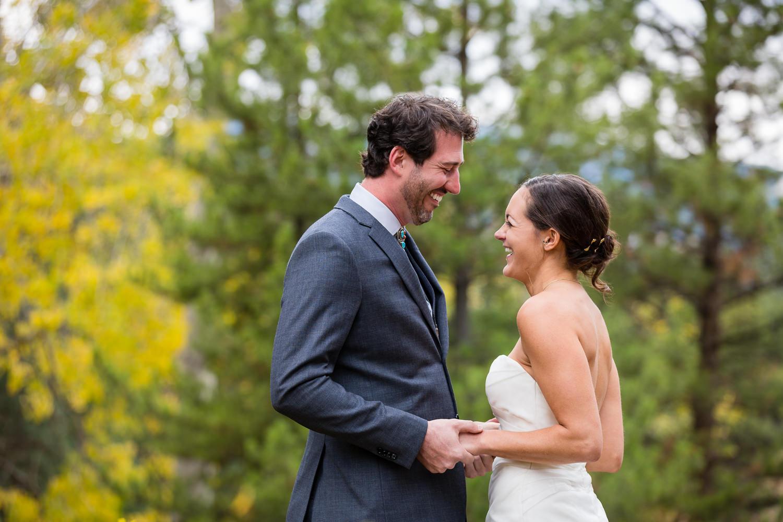 big-sky-montana-gallatin-riverhouse-wedding-bride-groom-laugh-while-holding-hands.jpg