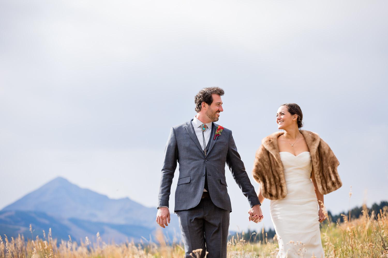 big-sky-montana-gallatin-riverhouse-wedding-bride-groom-walking-through-mountain-meadow.jpg