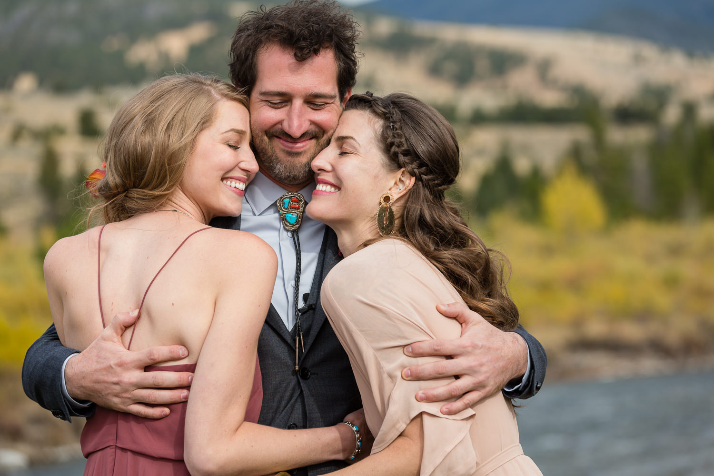 big-sky-montana-gallatin-riverhouse-wedding-groom-hugs-sisters.jpg