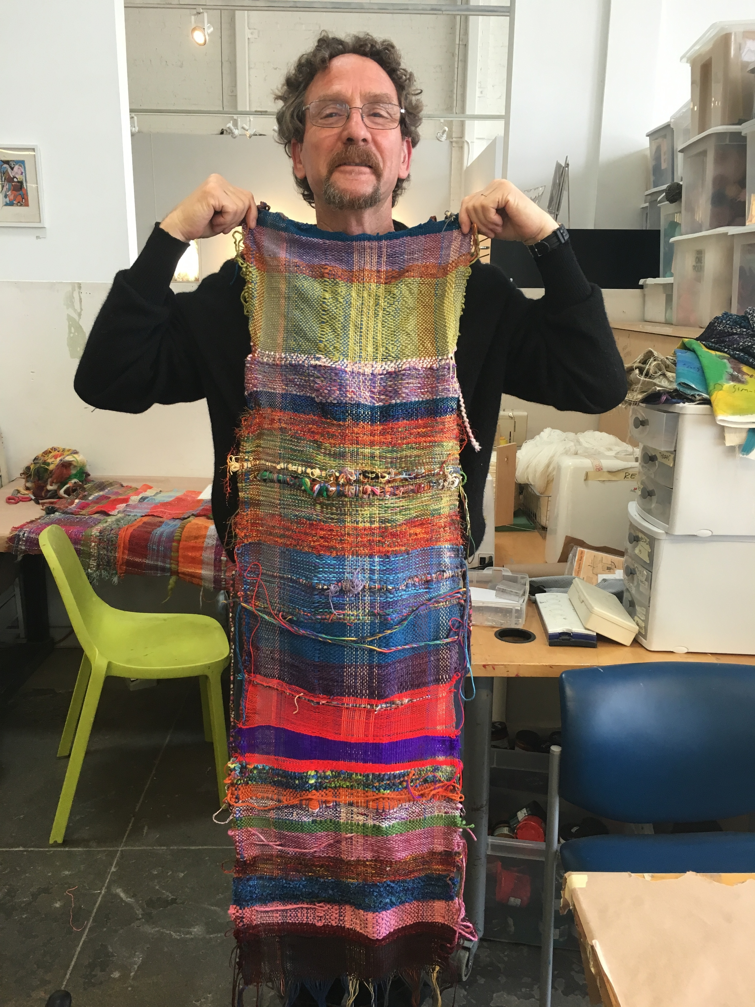 Artist Pete Salsman holding up the part of the communally woven piece pre garment making.