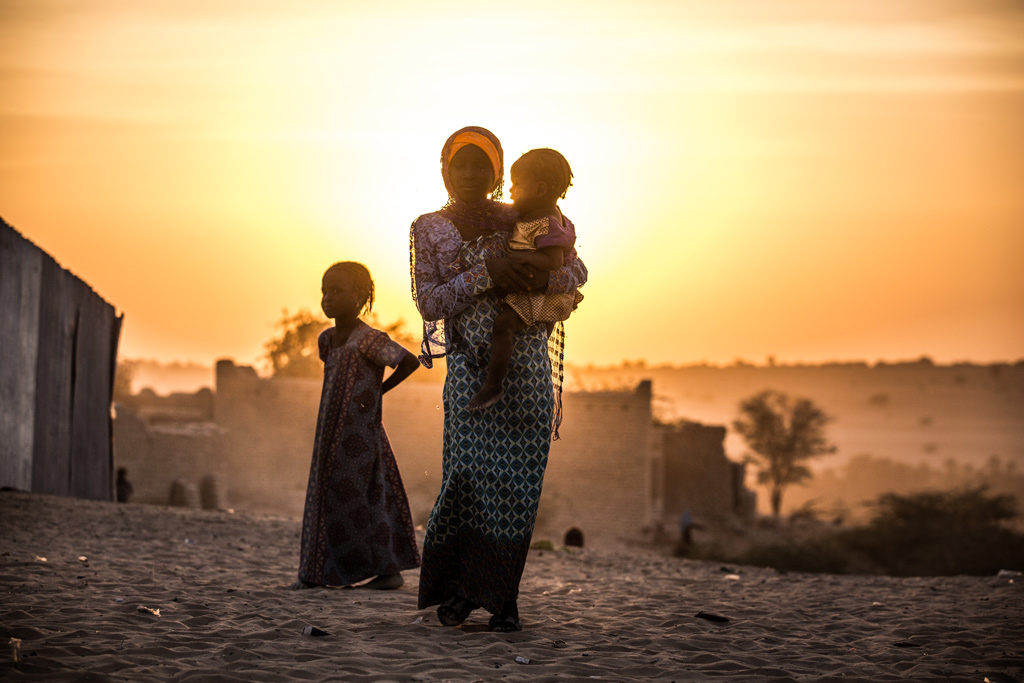 A girl carries her sister as another stands by her in the village of Mao in Chad. Photo: UNICEF/Tremeau
