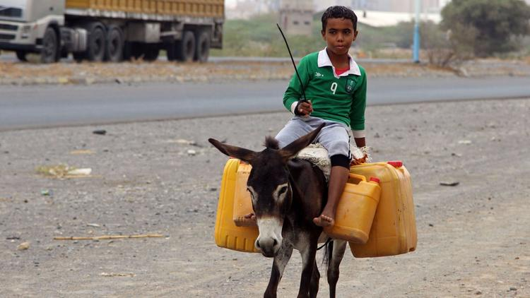 A boy carries water in plastic containers outside of Hodeidah, Yemen. (AFP/Getty Images)