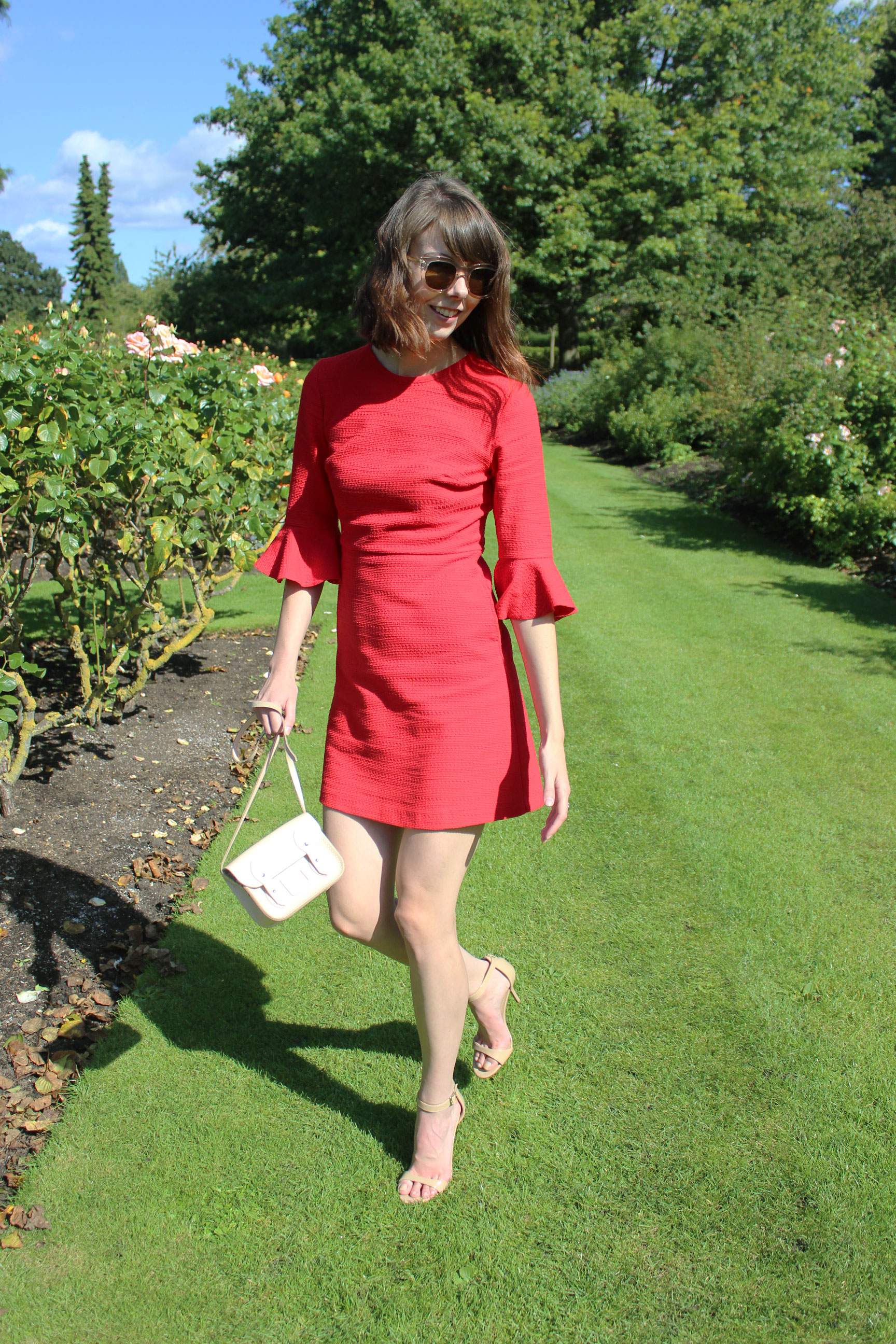 A red dress paired with neutral accessories.