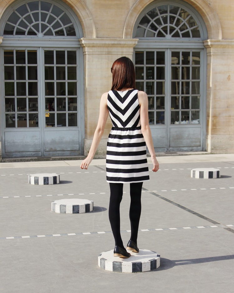 Wearing a black and white striped Loft dress and Everlane modern loafers at the Palais Royal in Paris.
