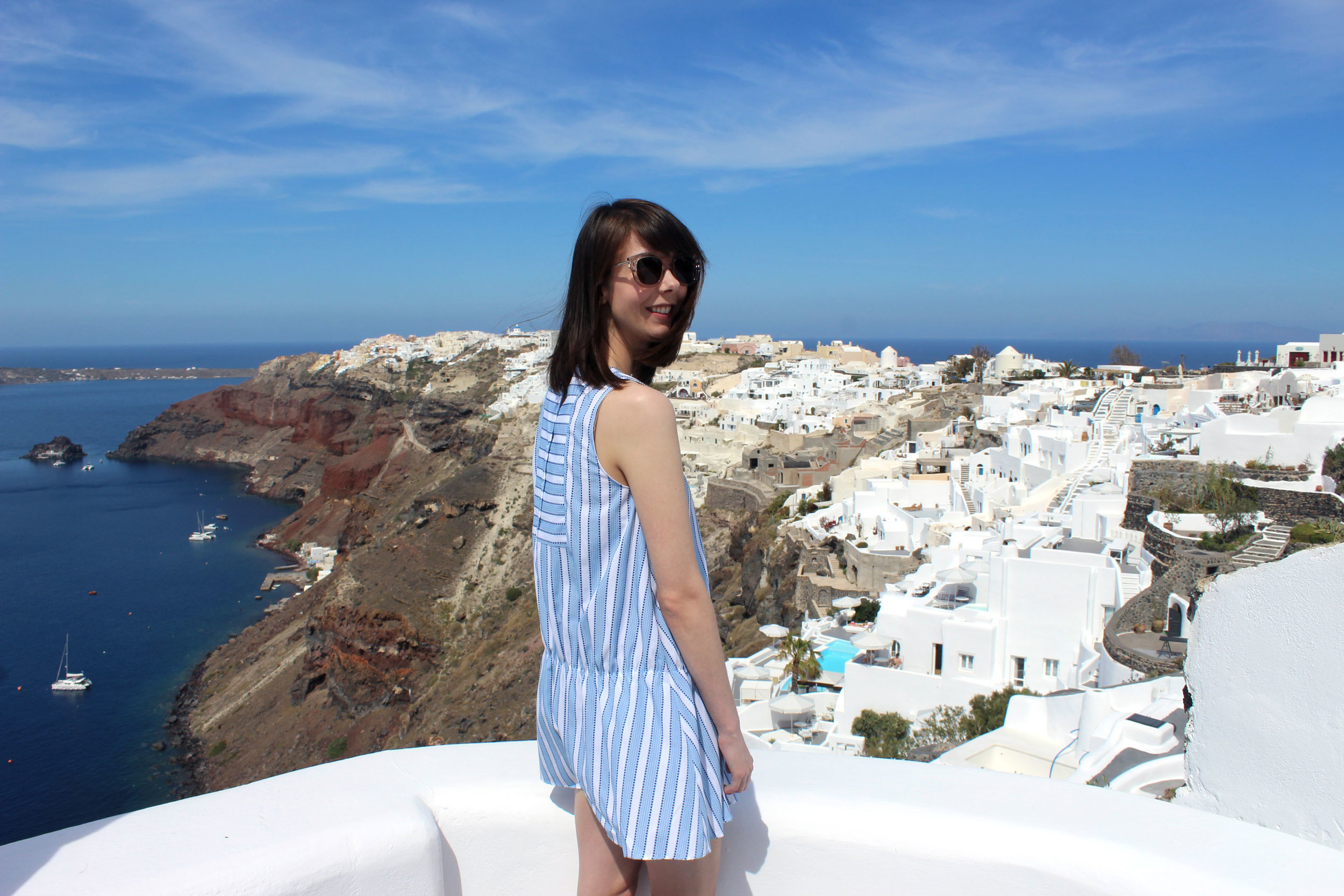 Standing on the balcony of our room at Ikies Hotel in Santorini, Greece.