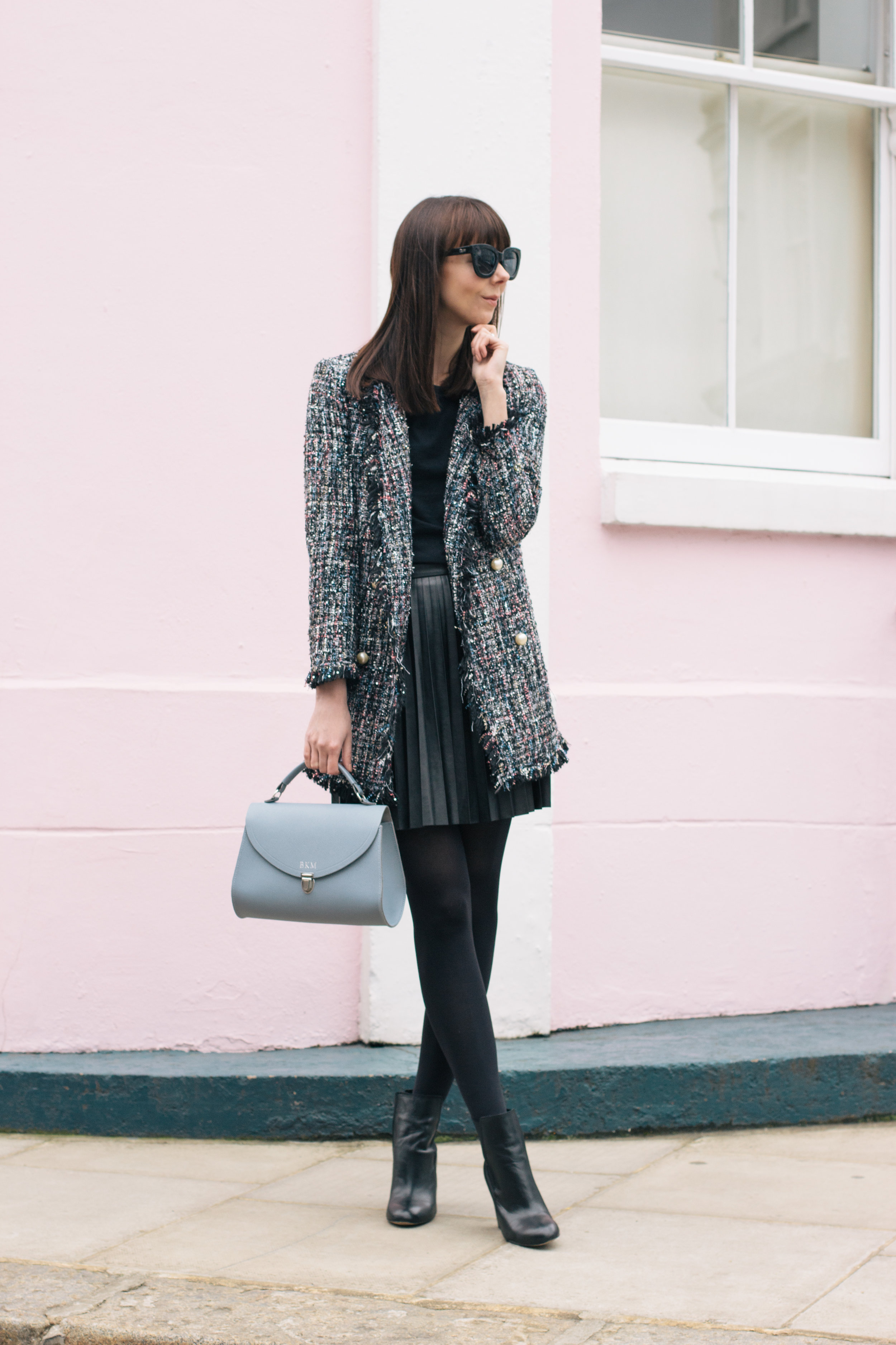 Wandering the colorful streets of Notting Hill wearing a Chanel lookalike jacket, a Cambridge Satchel Company bag, Sam Edelman booties and J.Crew pleated skirt | Pink House, Blue Bag | Sundays and Somedays