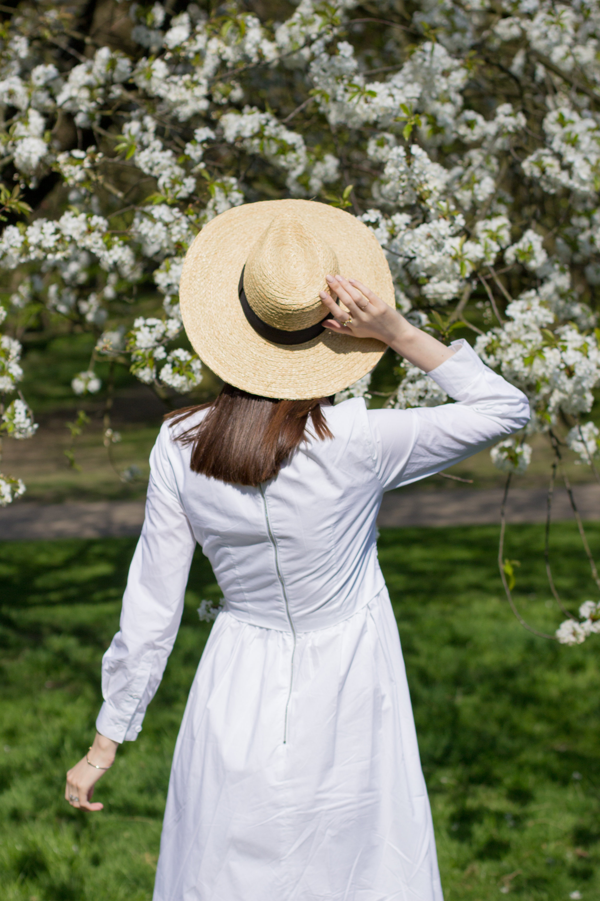 Exploring Kenwood House in Hampstead Heath, London wearing a summery white dress, straw hat, and bold sunglasses | Sundays and Somedays