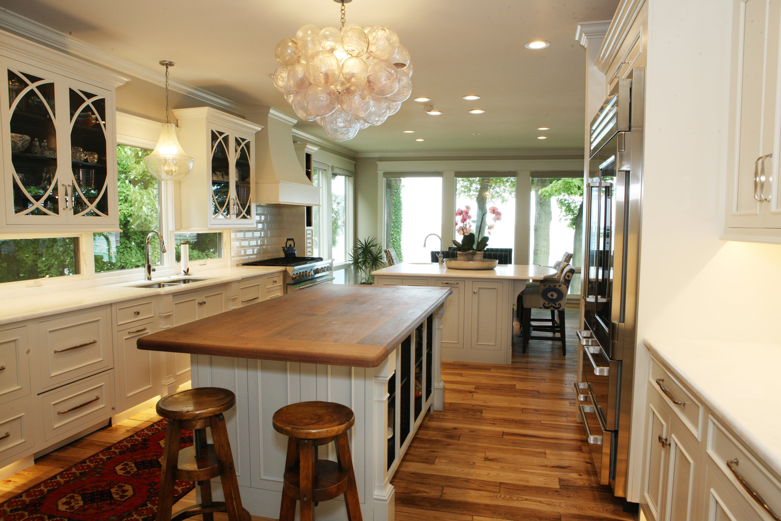 Stunning lighting from Traditions with a beautifully functional work island topped with wood.