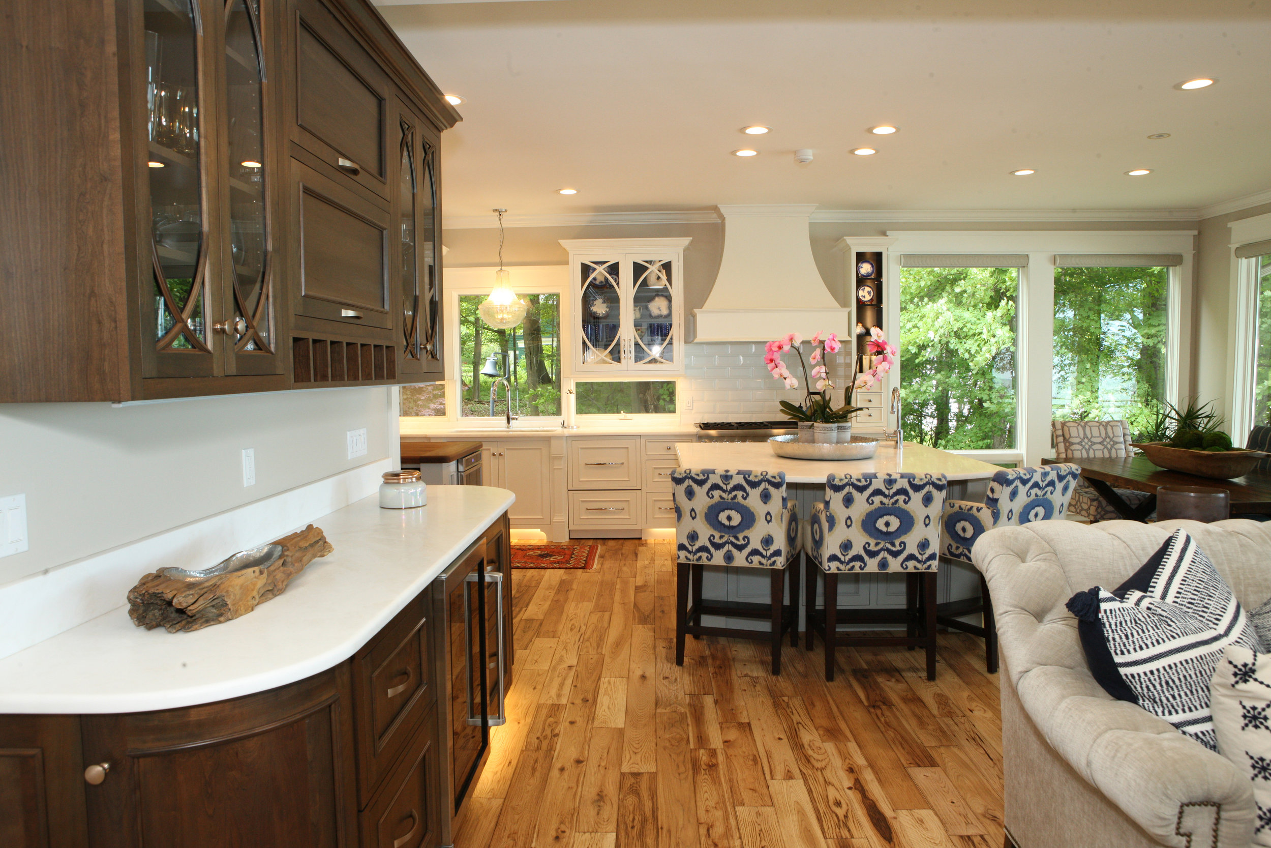 Warm hand scraped hickory floors leading up to sophisticated white cabinets, dark two-tone interiors.