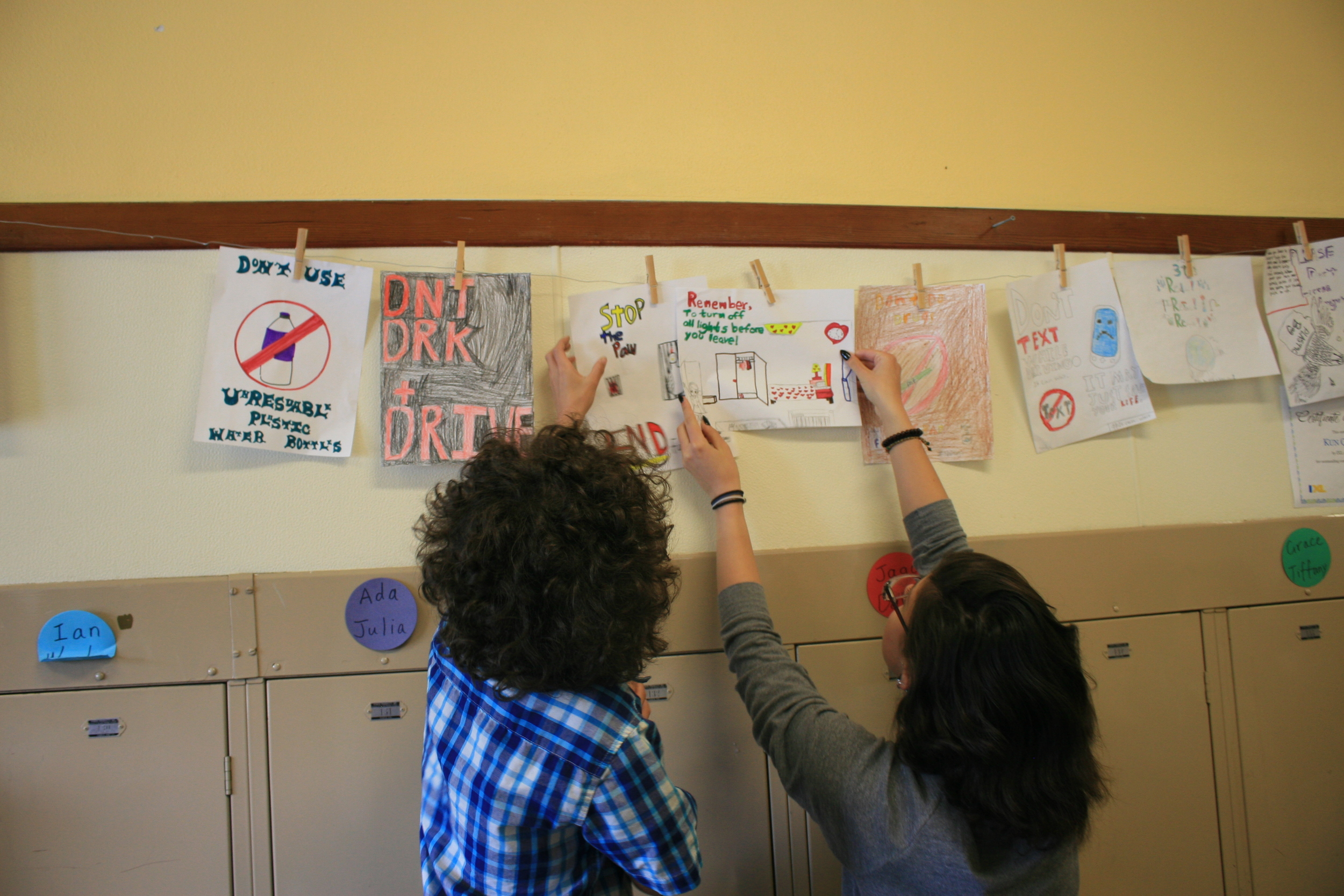 Students are helping each other hang their PSAs up after class.