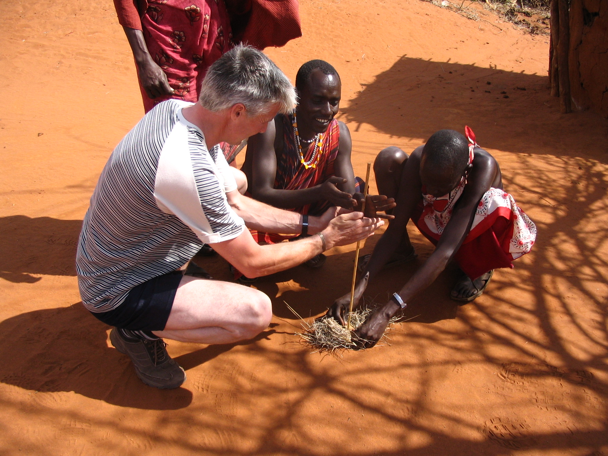 Maasai_people_and_a_tourist_lighting_a_fire_in_a_Maasai_village_on_the_A109_road,_Kenya.jpg
