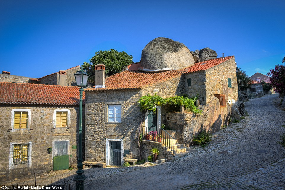 Villagers have formed their homes around the existing rocks, rather than attempt to move them