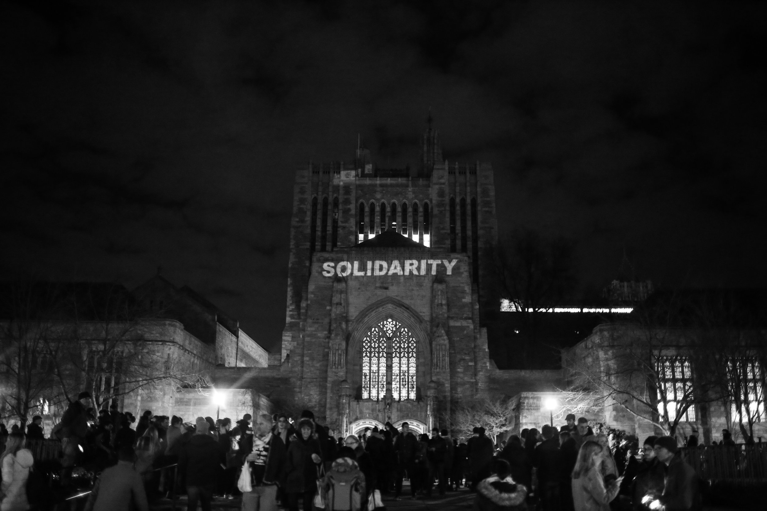 "New Haven, Connecticut - January 29th, 2017: A vigil is held for immigrants and refugees in front of Yale's Sterling Memorial Library. A projection onto the library reads ""Solidarity""."