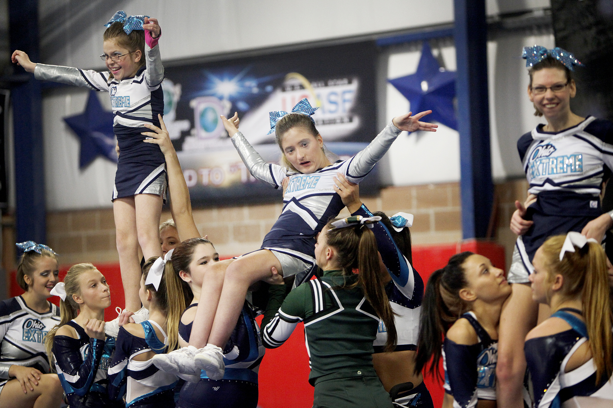 Emily Lezon is lifted in the air for a final pose during a performance at Tumbles and Cheers in Avon Saturday, November 2.