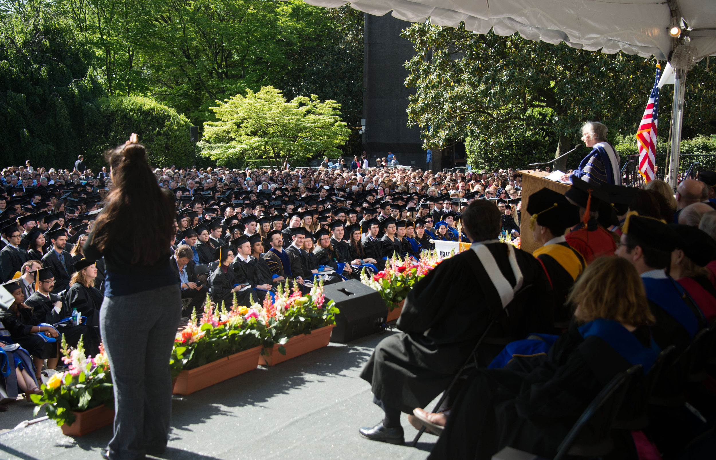 commencement speaker from previous year speaking to an audience of graduates on Healy Lawn