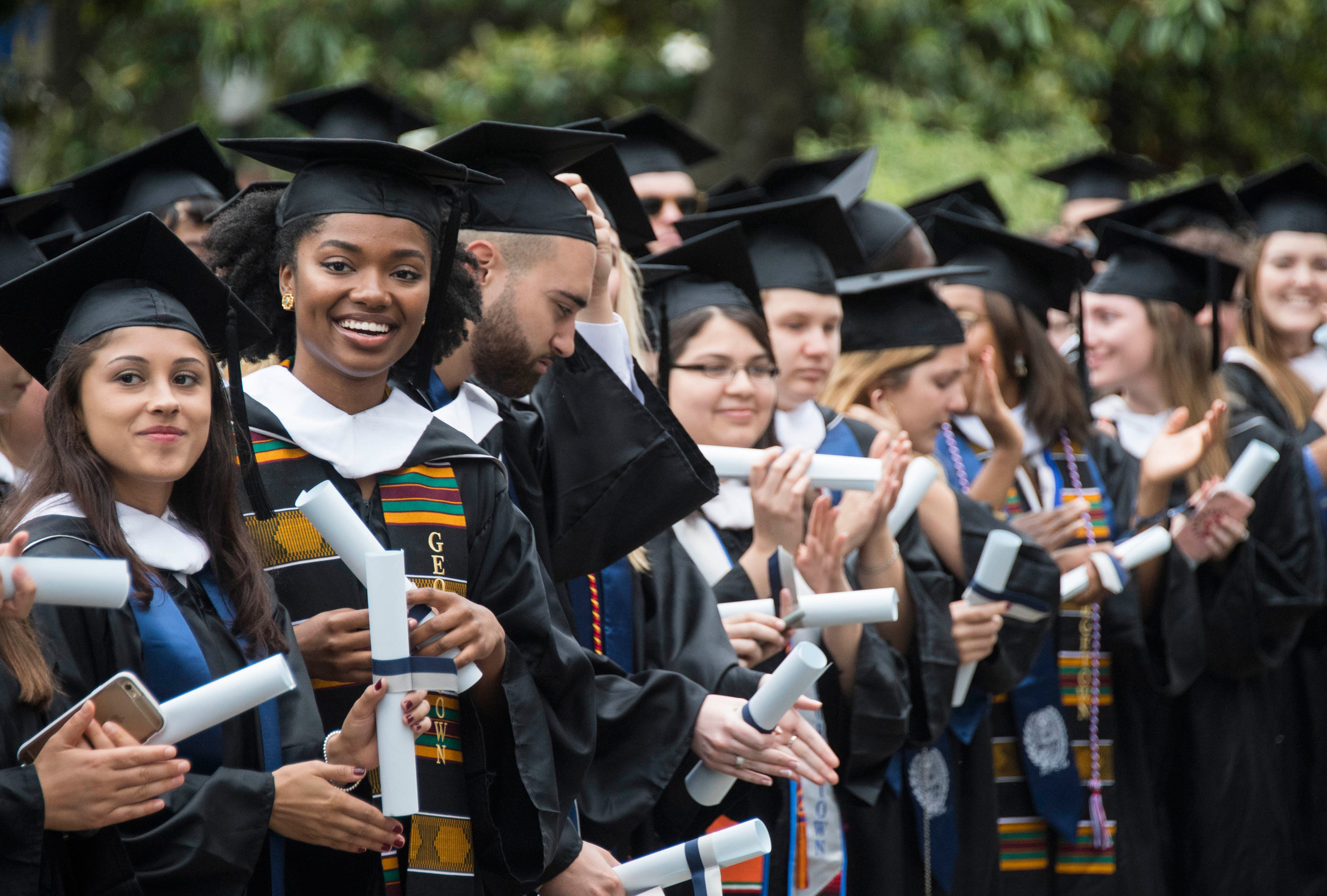 Graduates appalud as they prepare to walk the stage at commencement
