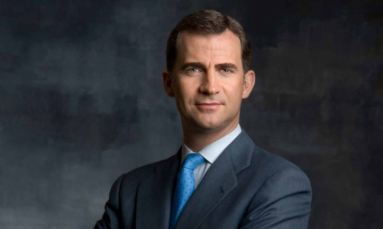 King Felipe stands in a suit for a portrait behind a gray background