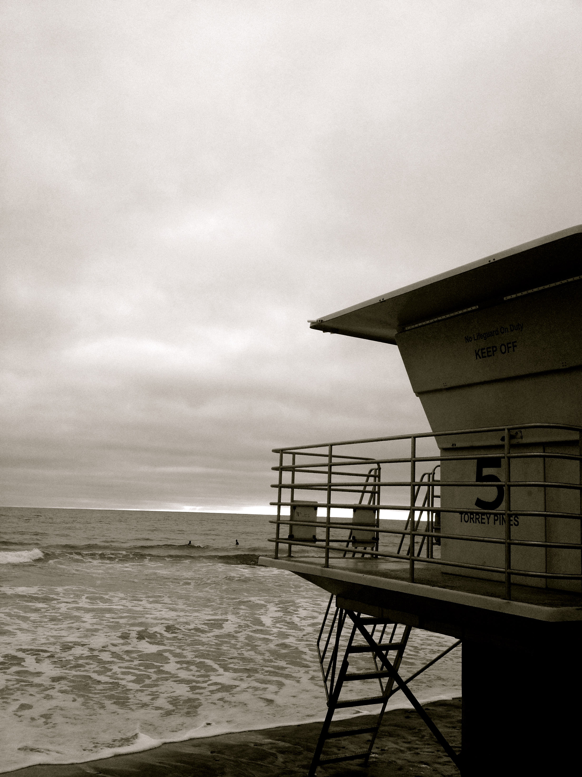 Lifeguard lookout sits vacant while two surfers await an evening wave.