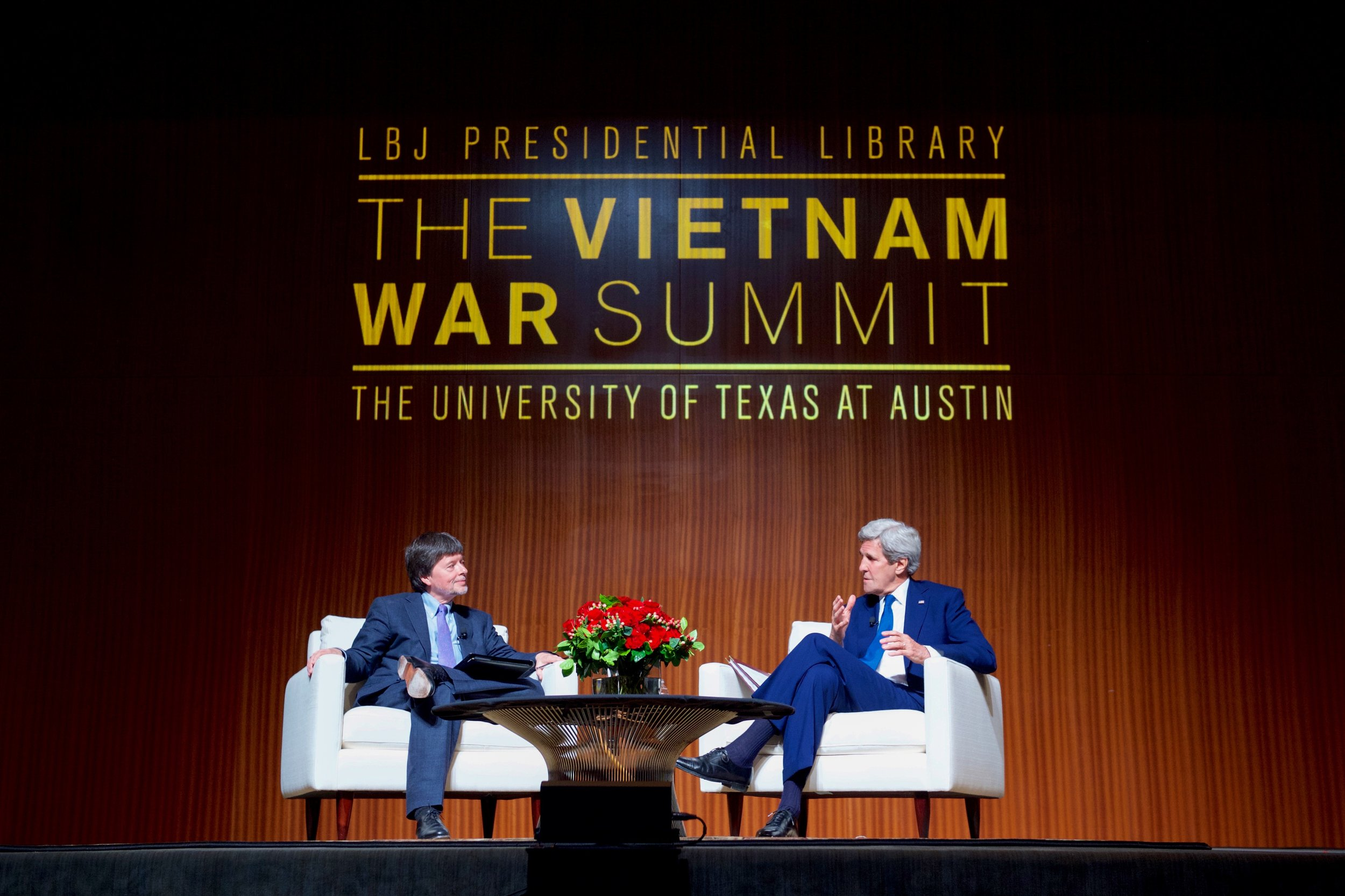 John Kerry talks with historian and filmmaker Ken Burns during a symposium focused on the Vietnam War.