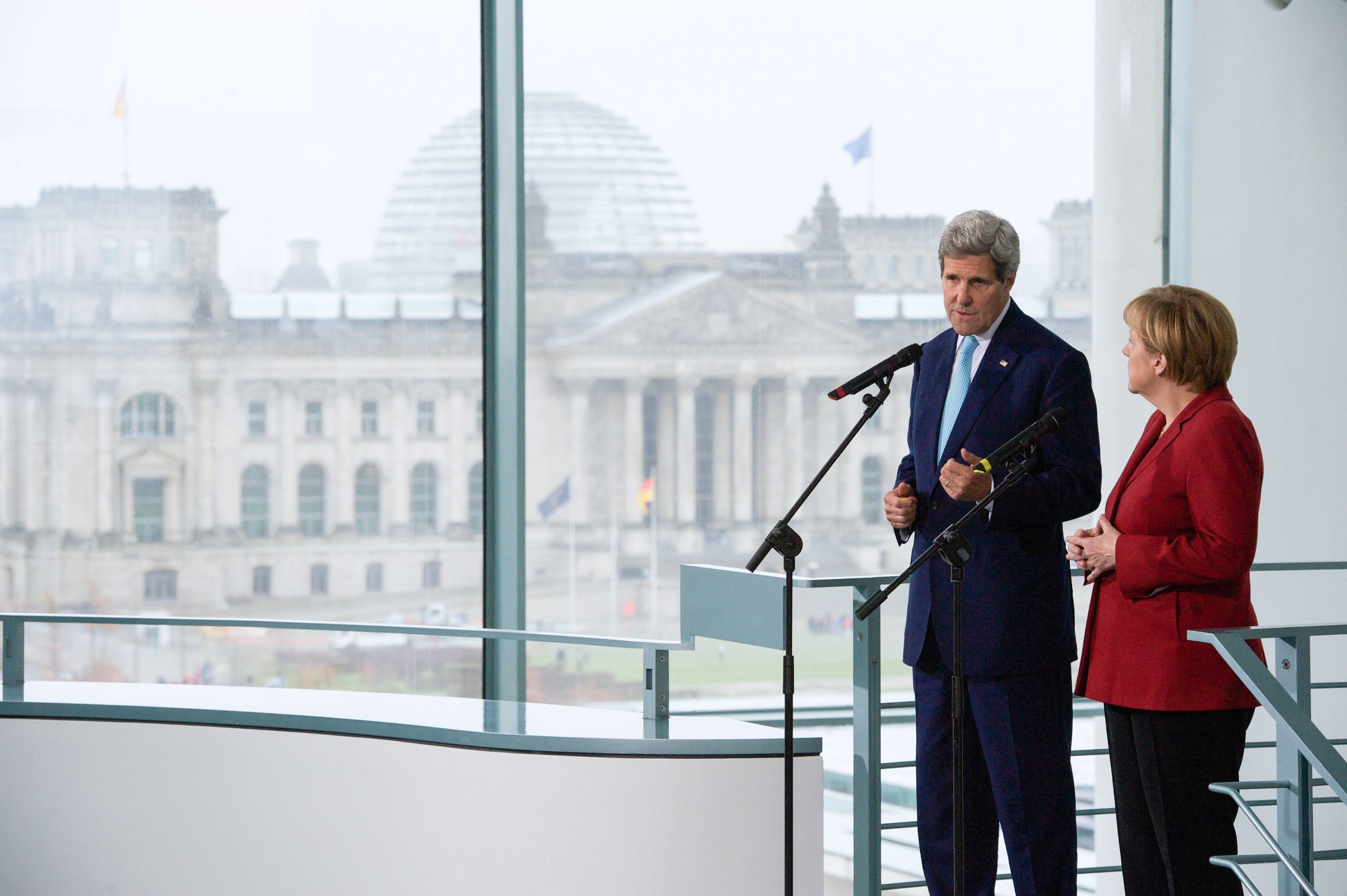Addressing reporters with German Chancellor Merkel as the Reichstag looms in the background.