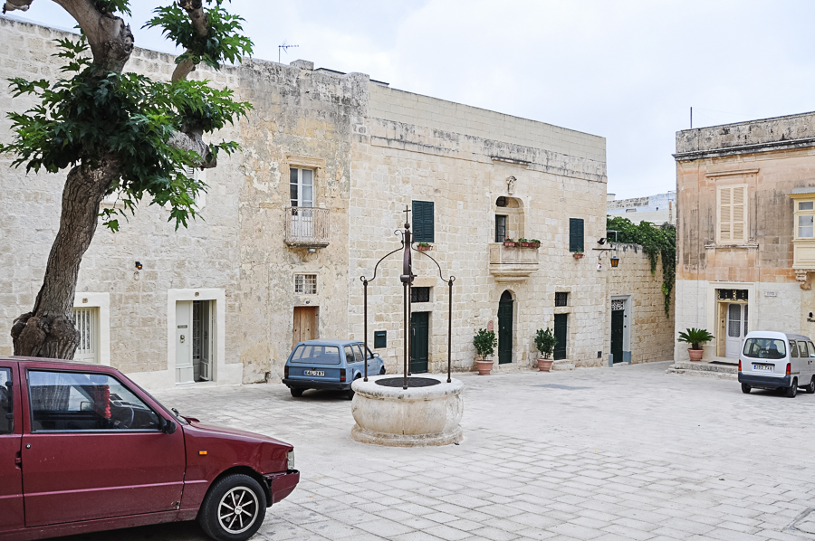 typical plaza of homes in Mdina, note the old well