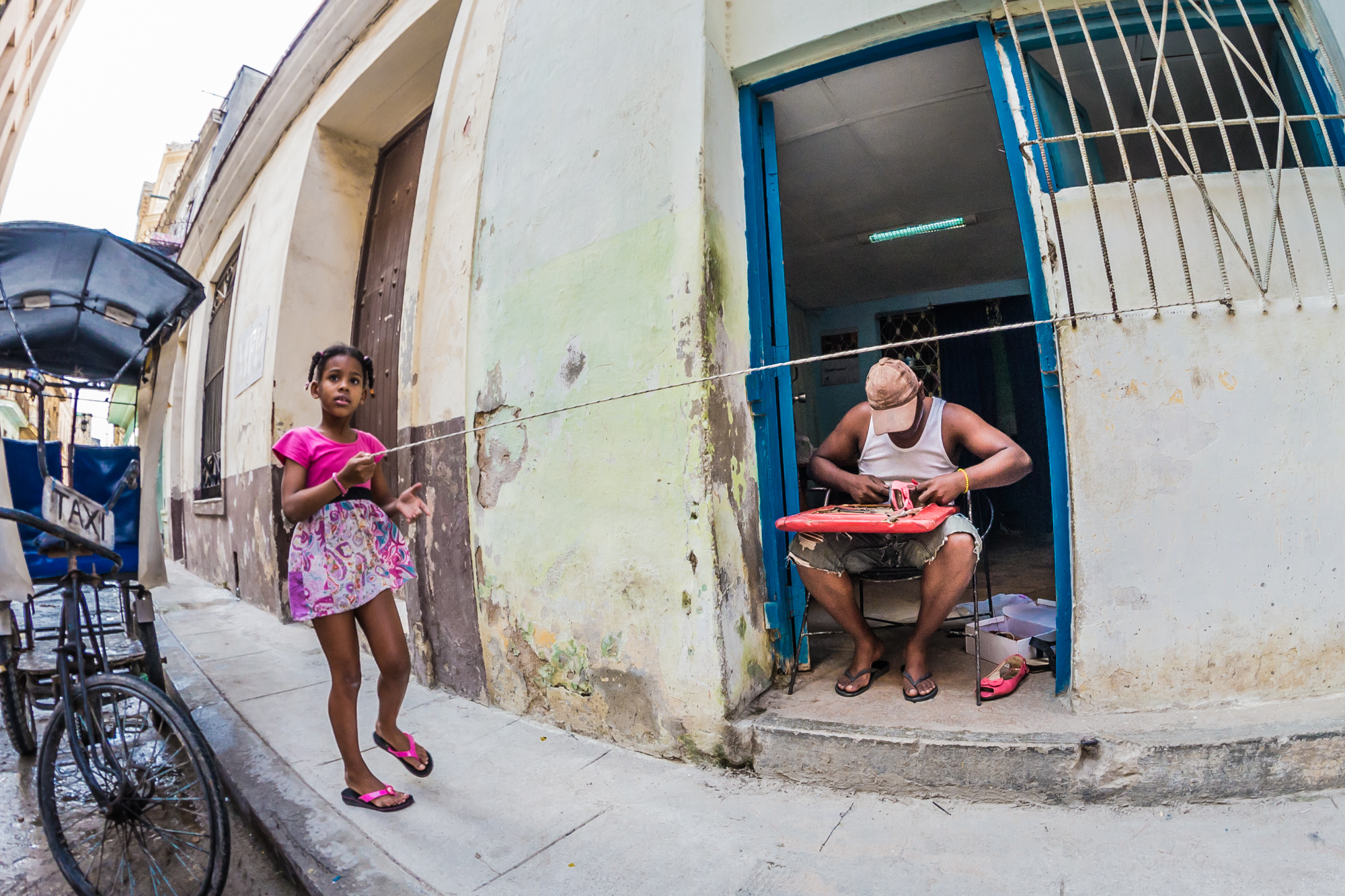 Life before iPads in Old Havana; a girl plays with a rope while her Dad repairs shoes