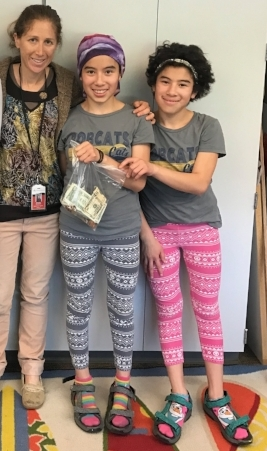 The girls and their teacher, Michelle, proudly hold their hard earned bake sale money!