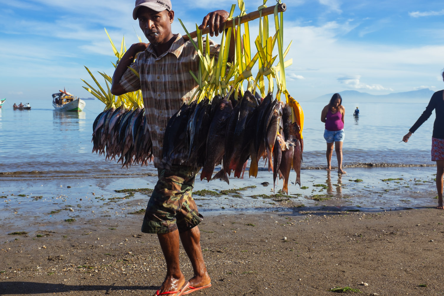 A fisherman walking off the ocean on a beach in central Dili