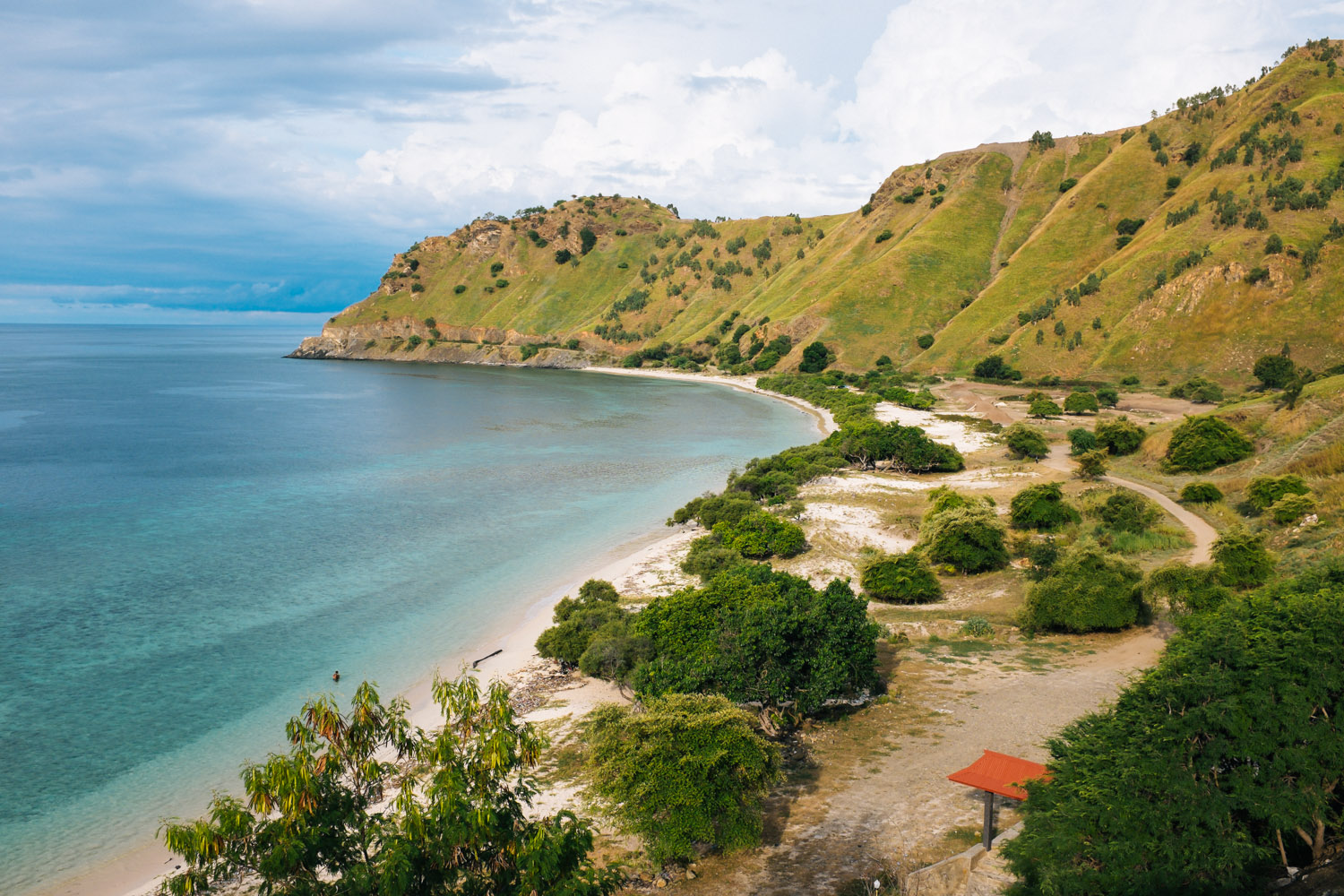An unspoiled beach surrounded by greenmountains in Dili