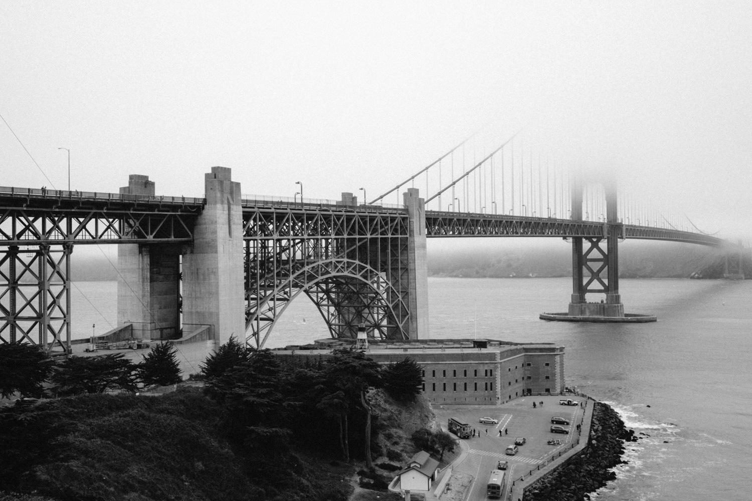 A monochrome view of the Golden Gate partially covered by the already characteristic fog