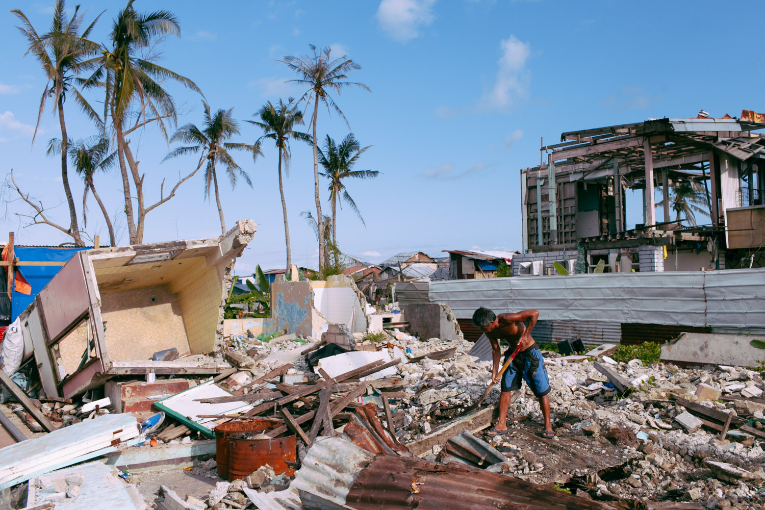 A man collects debris of what was left of his house after typhoon Haiyan (Yolanda) in Tacloban, Philippines.
