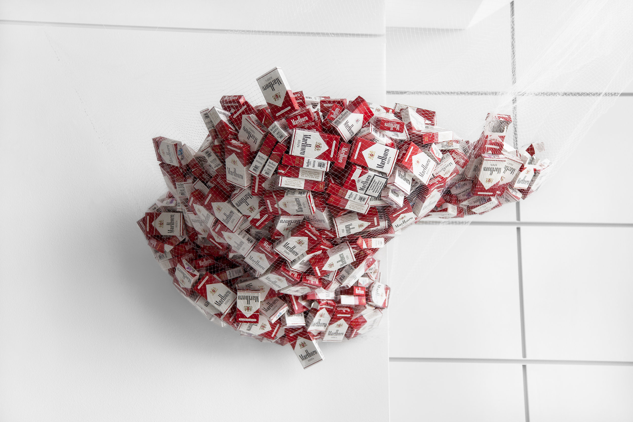 Pax  (ongoing), 2012-2014, approx. 730 consumed/ empty packs of Marlboro Reds 100's, minnow fishing net