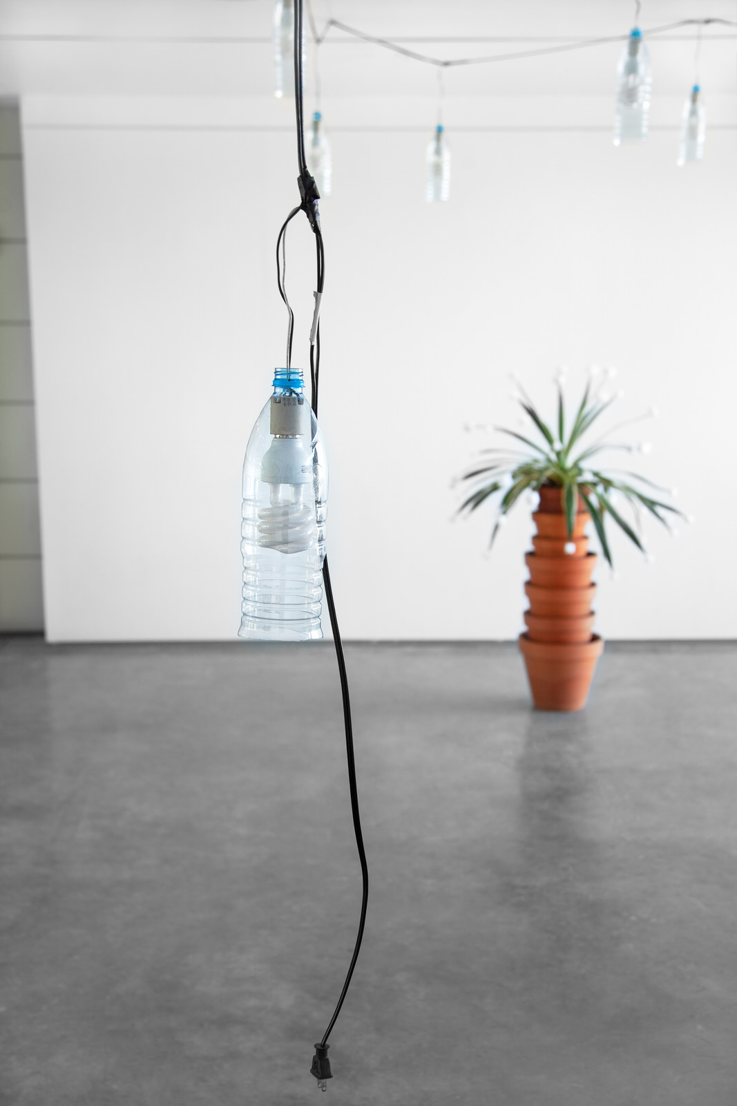 """String of Sohat , detail, 2014, 22 Sohat water bottles, 22 60W daylight bulbs, weather proof cable/ plug, 48' (576"""" long, 14.6 m)"""