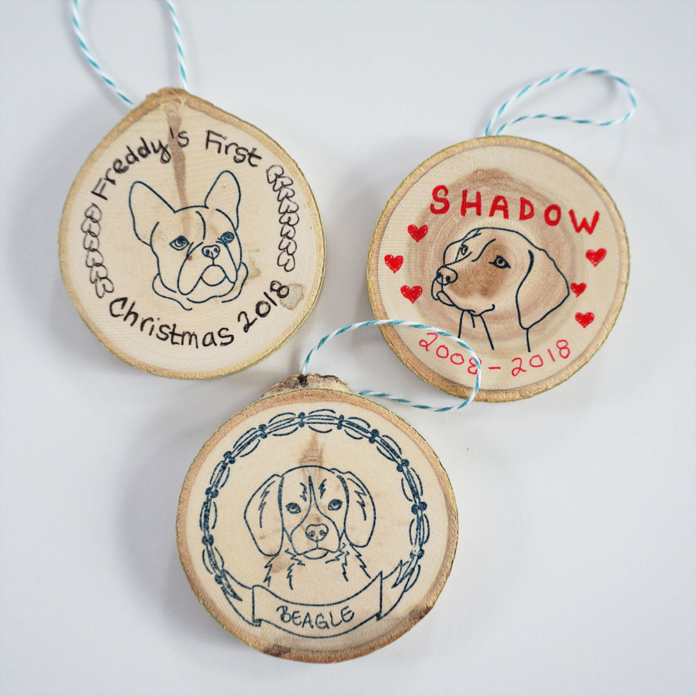 Whether you're celebrating your pup's first Christmas or have recently said goodbye to your best bud, making your own dog ornament is simple: here I used a tree slice (sanded), some StazOn ink (if you order a black or navy blue  ink pad  from us, you'll receive that brand), a piece of baker's twine adhered with hot glue, some regular ballpoint pens, and of course our  dog portrait stamps .