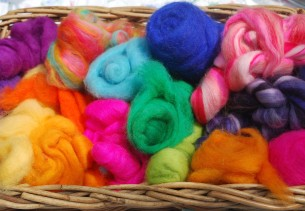 An assortment of colourful feting wool in a wicker basket