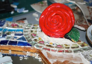 Close up of large ceramic rose set into a mosaic mirror
