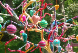 Needle felted decorations hanging on branched wrapped in wool