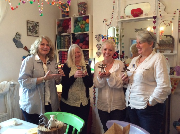 4 happy ladies proudly showing off their complex needle felted hares