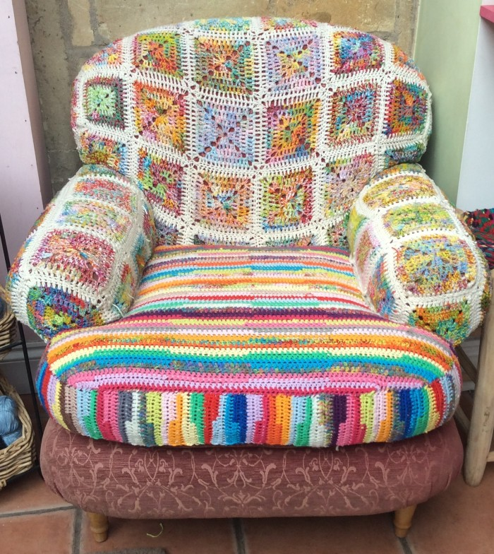 Armchair covered in crochet granny squares and cotton stripe