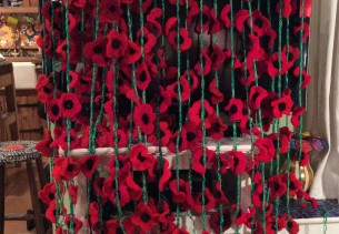 Crochet poppies for remembrance cascading over a tv