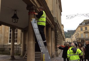 man up ladder fixing crochet poppies to a colonnade