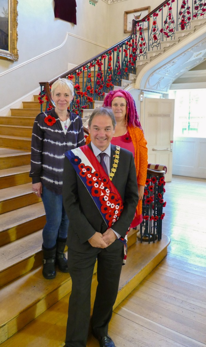 Emma Leith, Rosie Wilkes and councillor Martin Veal wearing the crochet sash