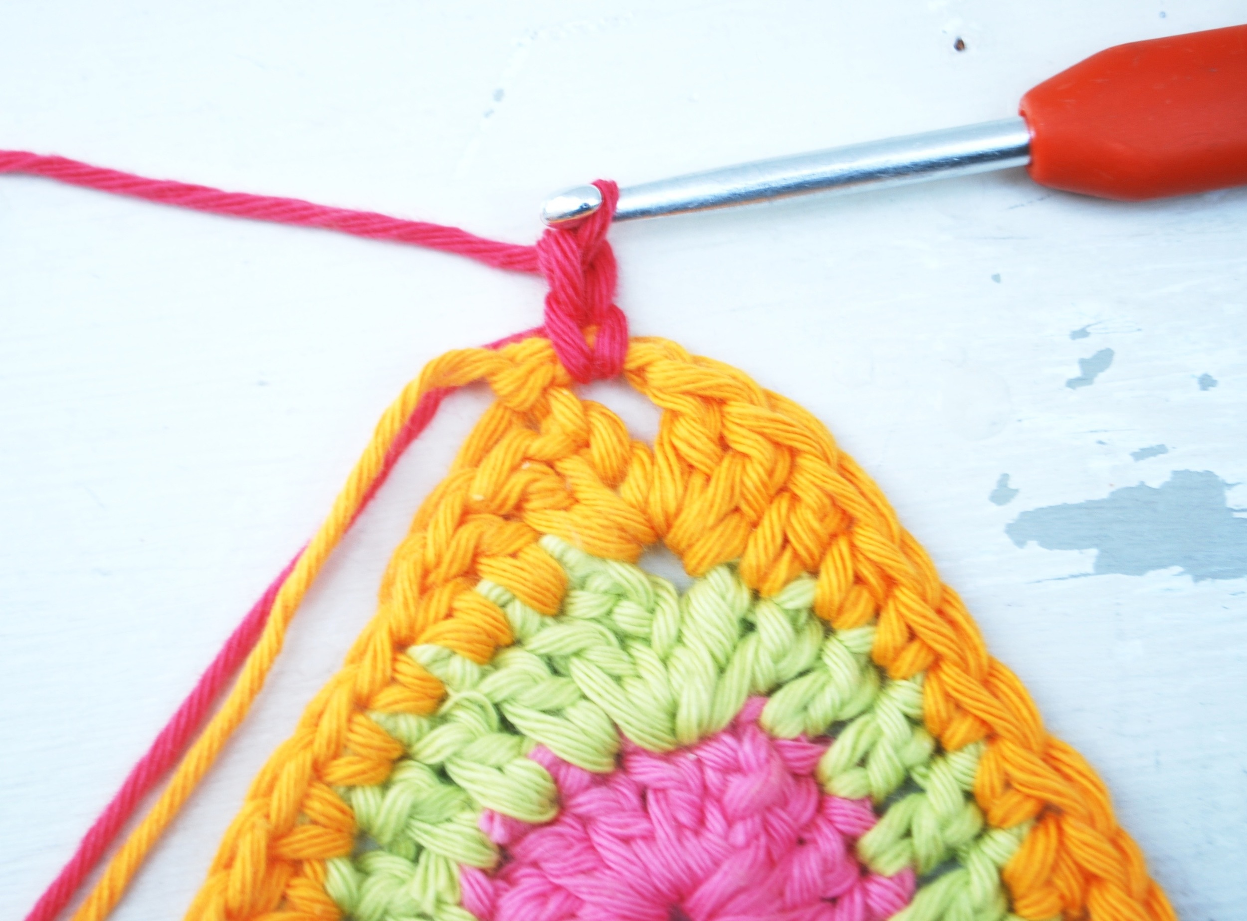 Join your final colour (Fuchsia) and worth chain 2 (this counts as your first halt treble crochet)
