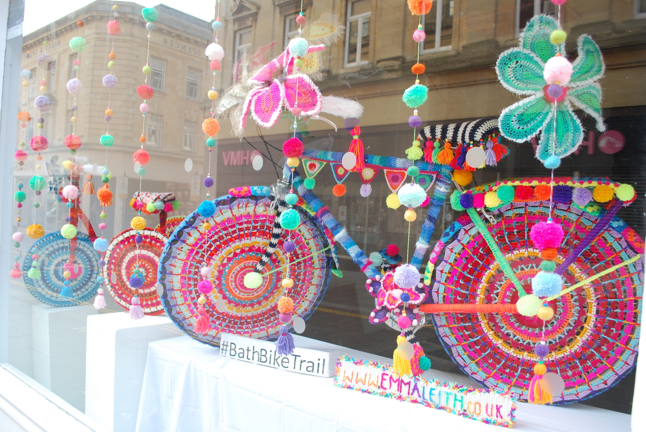 'Rio Carnival in Wool'. Yarn bomb bikes by Emma Leith in display in shop window in Bath