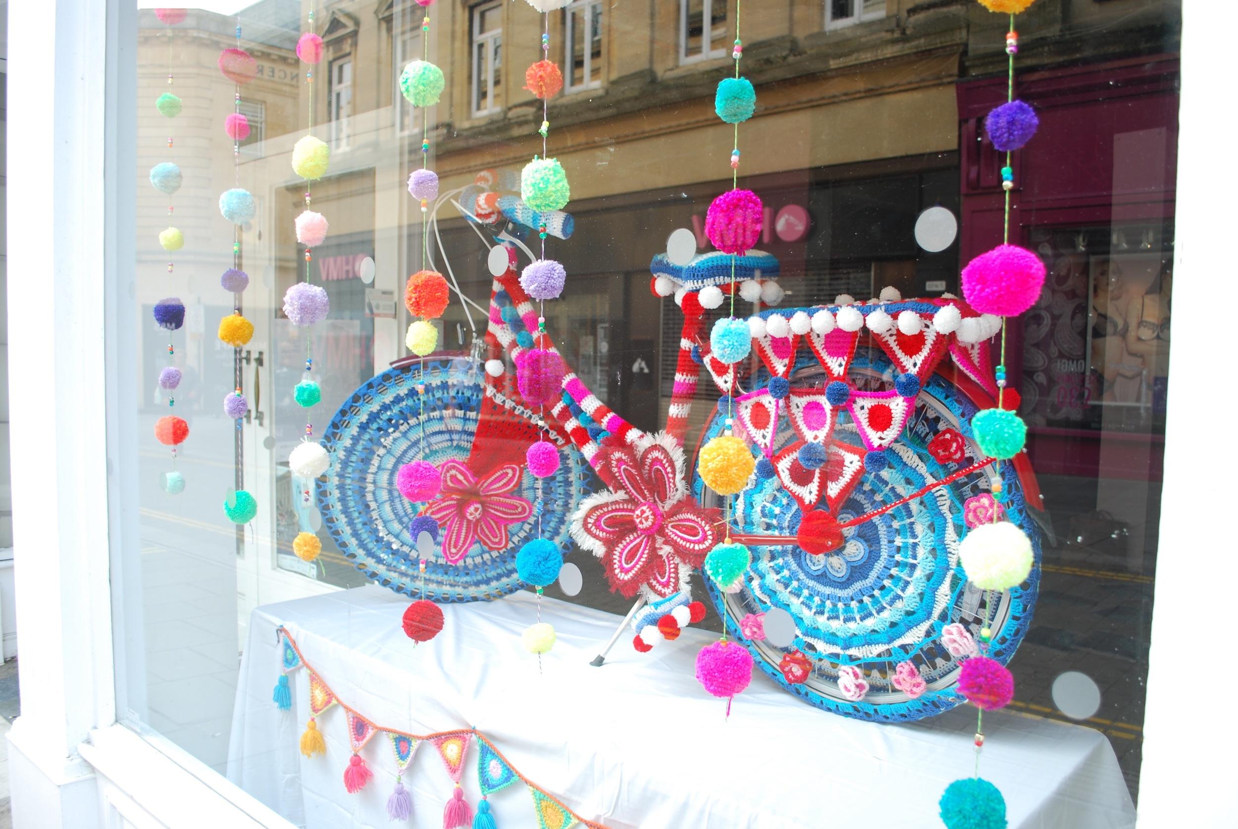 Yarn Bomb bike in shop window dispaly