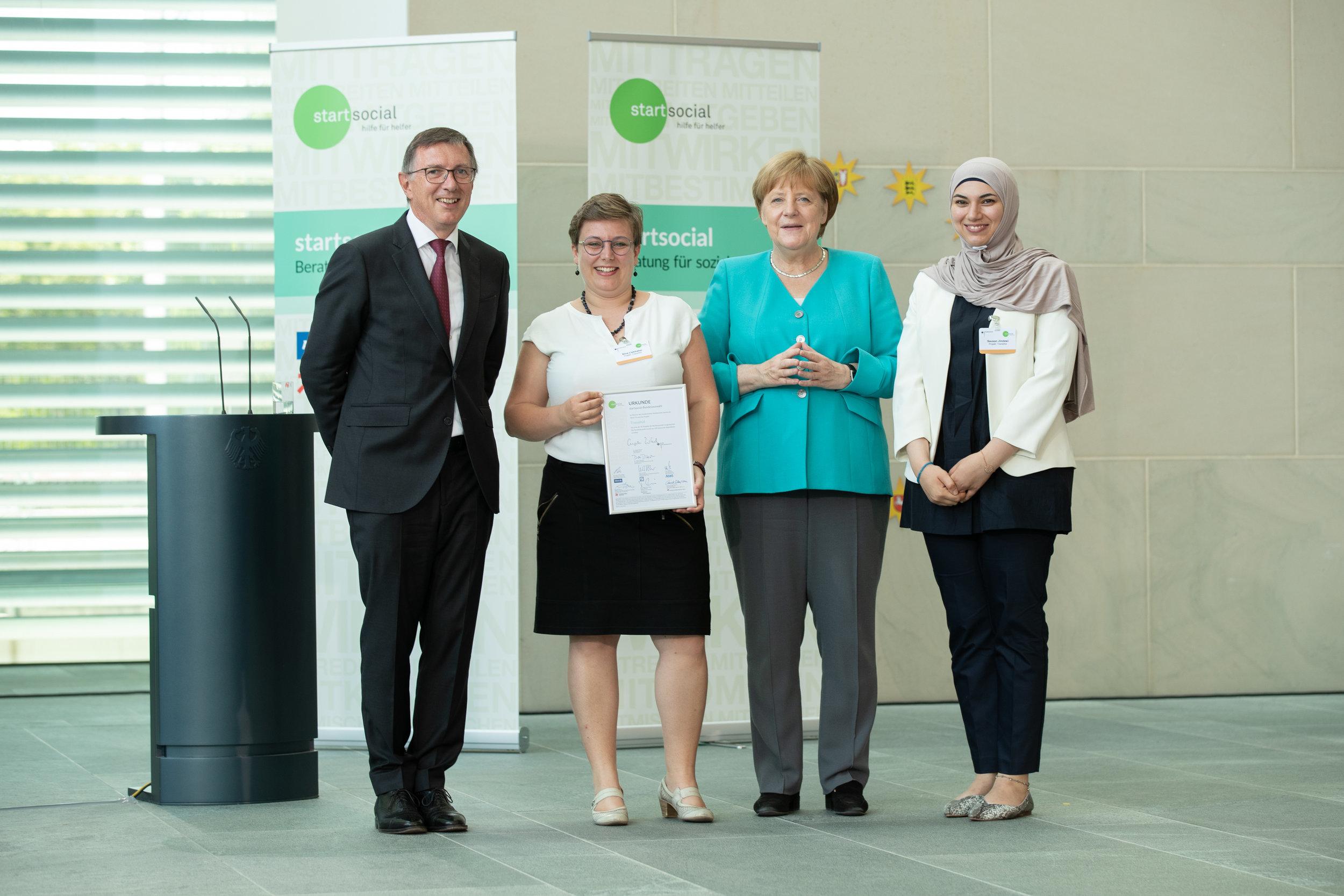 ©startsocial e.V./Thomas Effinger  von links nach rechts: Dr. Dieter Düsedau (Gründer von startsocial e.V.), Nina Liebhaber (TranslAid), Bundeskanzlerin Angela Merkel (Schirmherrin von startsocial e.V.), Sausan Jindawi (TranslAid)