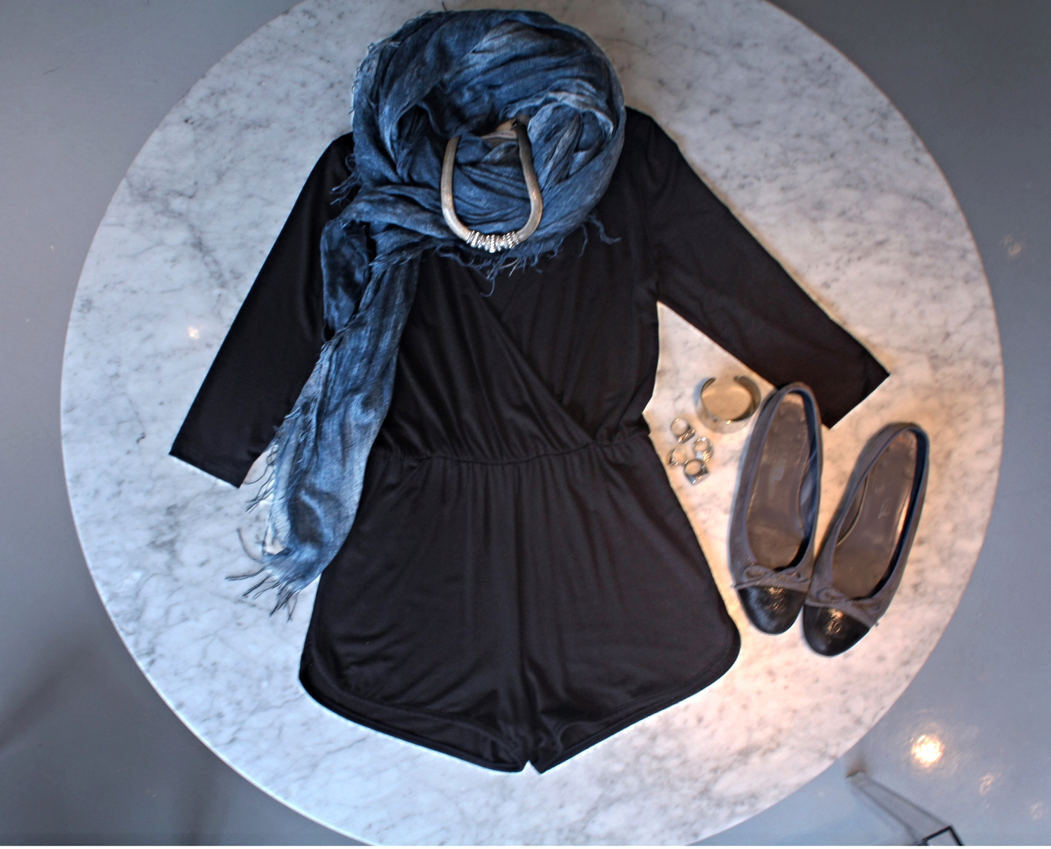 For a more laid back day look, this Vanity Room romper will leave you being comfy, and looking good! Pairing a scarf with a black romper brings a pop of color to the outfit.