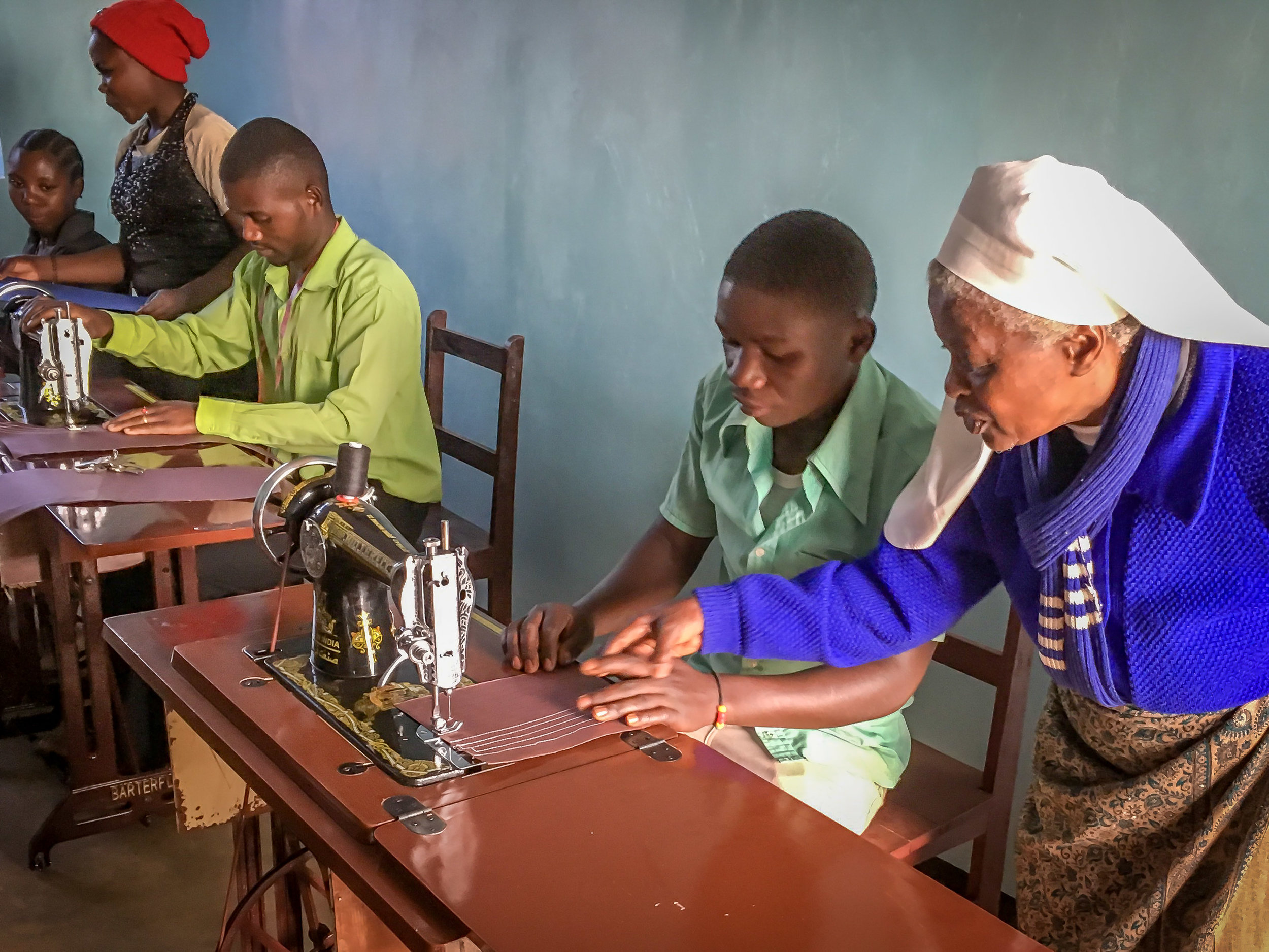 Sr. Magdalena teaching one of the young men how to sew straight lines.